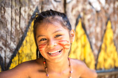 Native Brazilian girl smiling at an indigenous tribe in the Amazon.  royalty free stock image