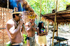 Native Brazilian group playing wooden flute at an indigenous tribe in the Amazon.  royalty free stock image
