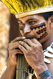 Native Brazilian guy playing wooden flute at an indigenous tribe in the Amazon Royalty Free Stock Photography