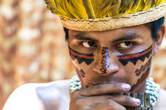 Native Brazilian guy playing wooden flute at an indigenous tribe in the Amazon Stock Photography