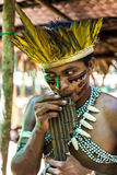 Native Brazilian guy playing wooden flute at an indigenous tribe in the Amazon.  royalty free stock photos