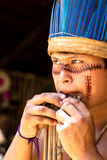 Native Brazilian guy playing wooden flute at an indigenous tribe in the Amazon Royalty Free Stock Photo