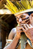 Native Brazilian guy playing wooden flute at an indigenous tribe in the Amazon Royalty Free Stock Images
