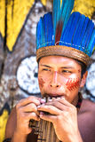 Native Brazilian guy playing wooden flute at an indigenous tribe in the Amazon royalty free stock photos