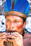 Native Brazilian guy playing wooden flute at an indigenous tribe in the Amazon Stock Photo