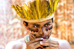 Native Brazilian guy playing wooden flute at an indigenous tribe in the Amazon Stock Image