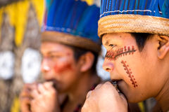 Native Brazilian guys playing wooden flute at an indigenous tribe in the Amazon Royalty Free Stock Images