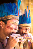 Native Brazilian guys playing wooden flute at an indigenous tribe in the Amazon Stock Photo