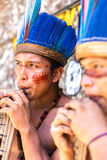Native Brazilian guys playing wooden flute at an indigenous tribe in the Amazon Stock Photography