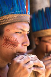 Native Brazilian guys playing wooden flute at an indigenous tribe in the Amazon.  royalty free stock photography