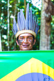 Native Brazilian man holding the Brazilian flag in the jungle in Amazon Stock Images