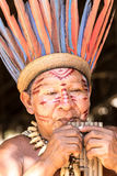 Native Brazilian man playing wooden flute at an indigenous tribe in the Amazon Stock Photos
