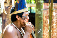 Native Brazilian man playing wooden flute at an indigenous tribe in the Amazon Royalty Free Stock Image