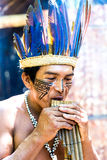Native Brazilian man playing wooden flute at an indigenous tribe in the Amazon Stock Images