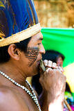 Native Brazilian man playing wooden flute at an indigenous tribe in the Amazon Royalty Free Stock Photography