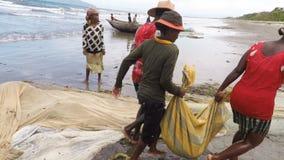 Native fishermen fishing on sea, woman selecting catched fish