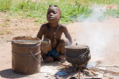 Native Himba boy. Cooking lunch Royalty Free Stock Photos