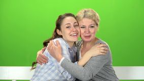 Native to embrace, they are sitting on a white bench. Green screen. Native hugs, they are sitting on a white bench, my mother and daughter are talking. Green stock footage