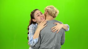 Native hugs, they are stand and talking. The daughter hugs her mother. Green screen.  stock footage