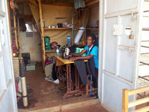 Native. This lady is working in this small hot shed. Running a sewing business, in a poor part of Africa. She will work long hours and still only make enough Stock Photos