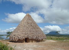Native landscape. Native home built with mud and straw on the coast of the river Carrao, in the Venezuelan Gran Sabana, Canaima National Park Royalty Free Stock Photos