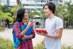 Native latin american female student talking with caucasian friend. Outdoors on campus of the university stock image