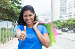 Native latin woman with blue shirt after shopping in city Royalty Free Stock Photos