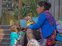 Native Mexican woman and child selling dolls in the streets of San Miguel de Allende royalty free stock photo