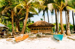 Native nipa hut with small fishing boats Stock Images