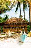 Native nipa hut with small fishing boats in front on beautiful white sand beach Stock Photos
