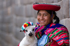 Native Peruvian holding a baby lamb. Cusco, Peru - May 14 : Jenni, a young woman dressed in colorful traditional native Peruvian closing holding a baby Lamb with royalty free stock images