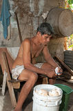 Native senior man cleaning slicing fresh coconut for production Stock Photos