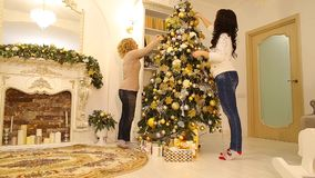 Native sisters amicably decorate Christmas tree and prepare for holiday, being in bright living room decorated in. Beautiful girls finish decorating Christmas stock video footage