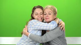 Native to embrace, they are sitting on a white bench. Green screen. Native hugs, they are sitting on a white bench, my mother and daughter are talking. Green stock video