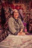 Native woman with headcloth in Kyrgyzstan. South Inylchek Glacier, Kyrgyzstan - circa August 2011: Smiling native woman with headcloth poses in her dwelling near Stock Photos