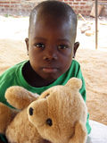 Native. An young African boy in a remote village, is not going to let go of the bear that a Geelong Mission worker from Australia has given him. Missionary Stock Image
