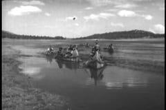 Nativi americani che remano giù il fiume sulla canoa video d archivio