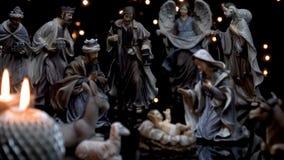 A natividade do comedoiro do Natal figura a cena com luzes das velas video estoque