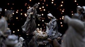 A natividade figura o comedoiro do Natal da cena com luzes video estoque
