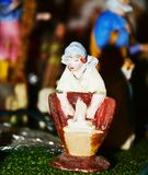 Nativity scene, Christmas detail, Italian traditions. Female statue cooking and blurred background, detail from a nativity scene in north Italy, close up Stock Photography
