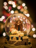 Nativity Scene Snow Globe. This is a snow globe depicting the Nativity. A Christmas tree with lights is in the background Royalty Free Stock Photo
