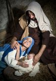 Nativity scene in a stable. Live Christmas nativity scene in an old barn - Reenactment play with authentic costumes.  The baby is a property released doll Royalty Free Stock Photos