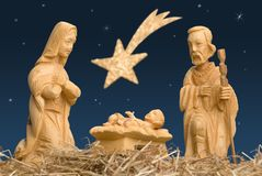Nativity Scene with Star of Bethlehem. Wooden figures of Mary and Joseph watching baby Jesus, with night sky and comet royalty free stock photo