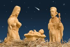 Nativity Scene with Star of Bethlehem. Wooden figures of Mary and Joseph watching baby Jesus, with night sky and comet royalty free stock photography