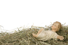 Nativity scene on white background. Baby Jesus figurine lying on hay royalty free stock photo