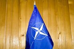 NATO flag. NATO  flag on wooded background Royalty Free Stock Photos