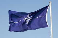NATO-Flag. On flagpole, waving in the wind. Blue sky royalty free stock photos