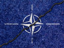 NATO flag painted on cracked wall background/Divided NATO concept royalty free stock photos