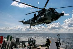 NATO rescue mission in sea with ship and helicopter. Helicopter rescue mission in difficult stormy weather at sea. NATO military helicopter and ship in Baltic stock photo
