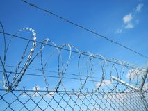 Nato Wire. Barbed Wire against bright blue sky. Security fence at the airport or campsite royalty free stock photo